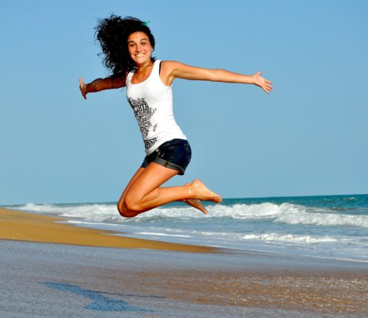 Fit Woman at the Beach Jumping